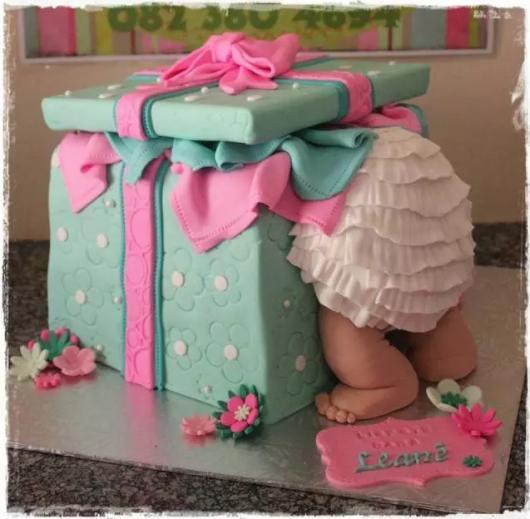 Bolo Chá Revelação de pasta americana no formato de presente com bebê saindo de dentro da caixa