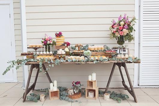 Chá de Casa Nova decoração feita com mesa rústica, vasos de flores e velas