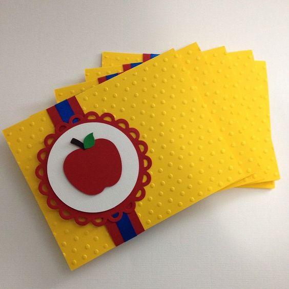 Envelope amarelo, com desenho de maça e fita vermelha e azul.