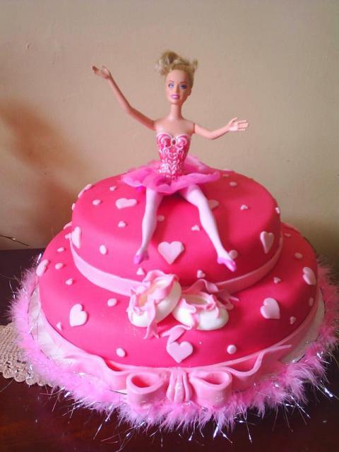 Bolo da Barbie com predominância da cor pink e boneca no topo