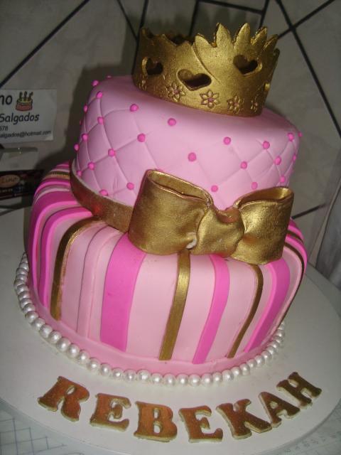 Bolo de Princesa rosa decorado com coroa e laço dourado