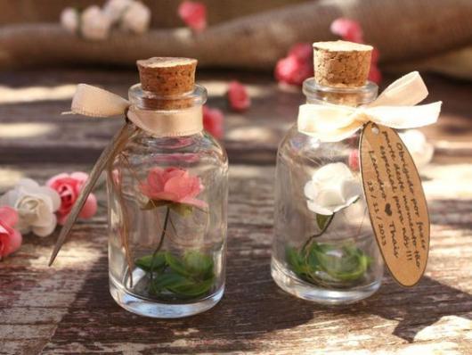 Potinhos de vidro para lembrancinhas com flor dentro.
