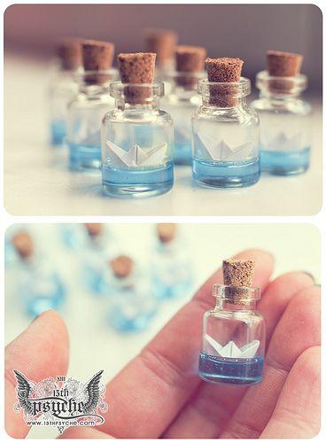 Potinhos de vidro para lembrancinhas com barquinho de papel dentro.