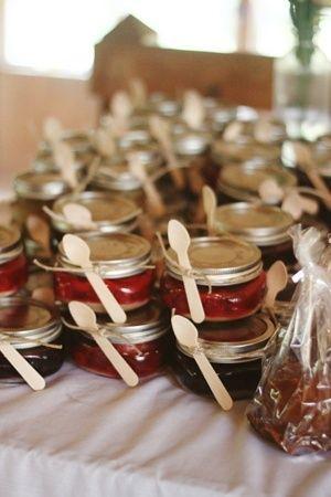 Potinhos de vidro para lembrancinhas com doce dentro e colherzinha.