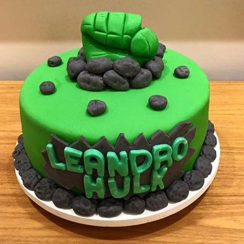 Bolo do Hulk decorado com nome do aniversariante e topo de punho verde saindo de rochas