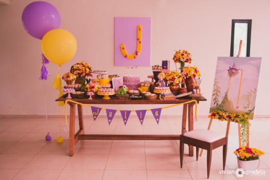 Festa Rapunzel simples decorada com mesa rústica e painel de papel