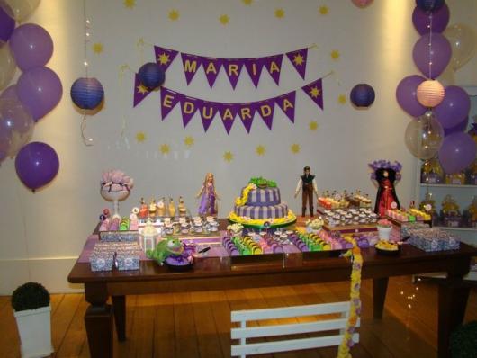 Festa Rapunzel simples decorada com mesa rústica balões e varal de bandeirinhas