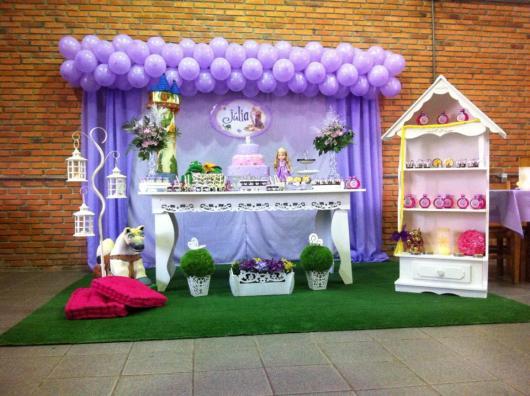 Festa Rapunzel provençal decorada com tapete de grama e armário de lembrancinhas no formato de castelo