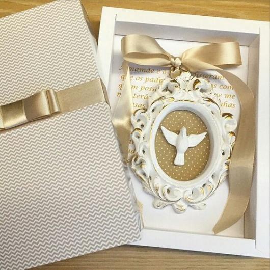 Caixa branca com decoração em dourado.