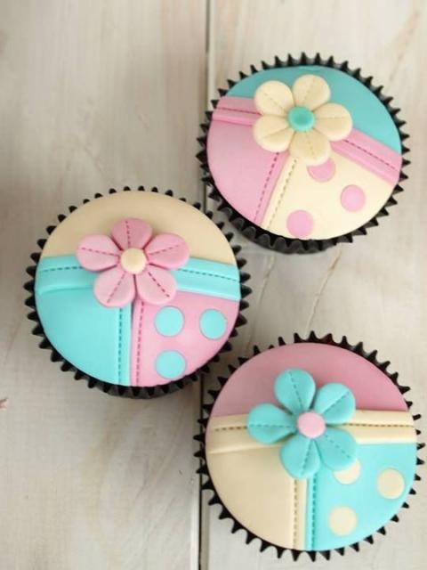 Cupcakes decorados com as cores amarelo, rosa e azul.
