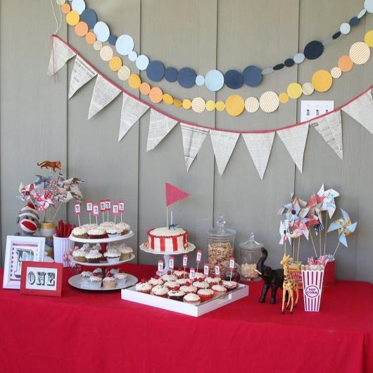 Mesversário decoração do Circo com varal de bandeirinhas e toalha de mesa improvisada vermelha