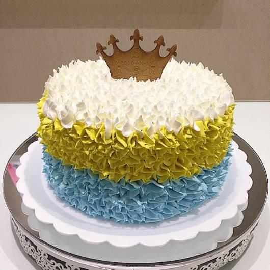 Bolo de Aniversário Simples com chantilly azul, dourado e branco e topper de coroa