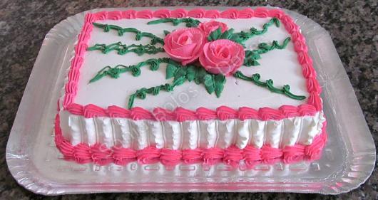 Bolo Dia das Mães decorado com chantilly branco e rosa e flores com folhas verdes