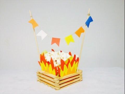decoração de festa junina simples centro de mesa no formato de fogueira com pipoca