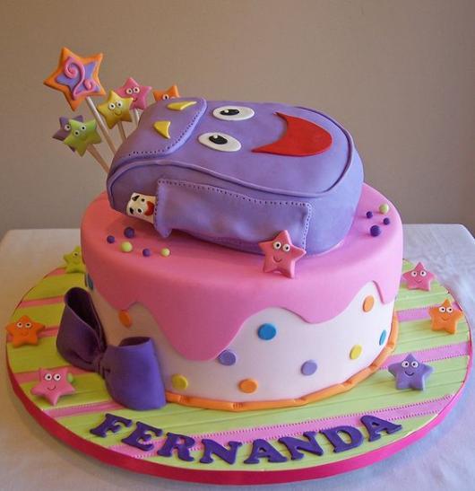 Bolo da Dora Aventureira com mochila roxa no topo.
