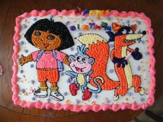 Bolo com personagens da Dora Aventureira desenhados com chantilly.