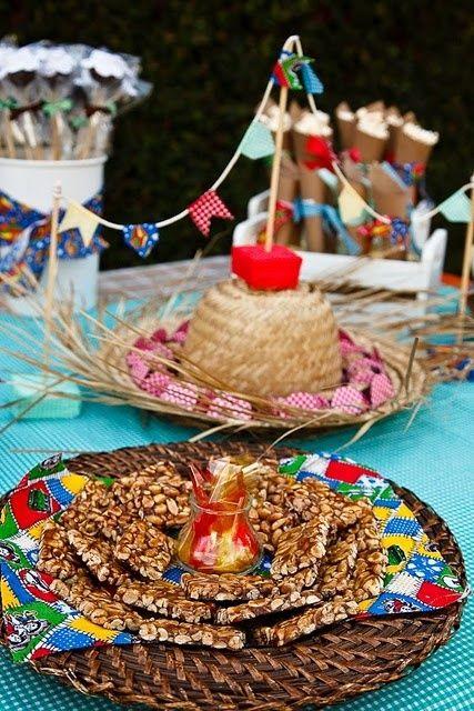 Mesa com chapéu de palha e doces.
