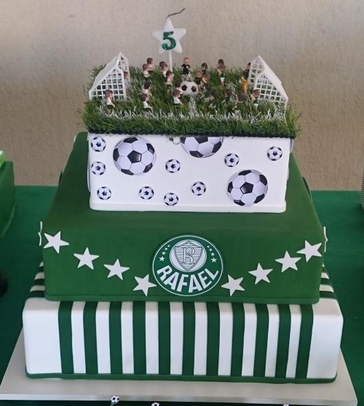 Um bolo quadrado de três andares com um topo lindo imitando o campo de futebol