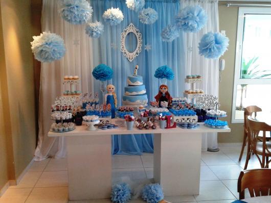 Decoração de festa infantil Frozen com cortina azul e branca