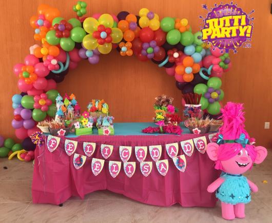 Aposte no arco de balões para decorar a mesa da festa Trolls
