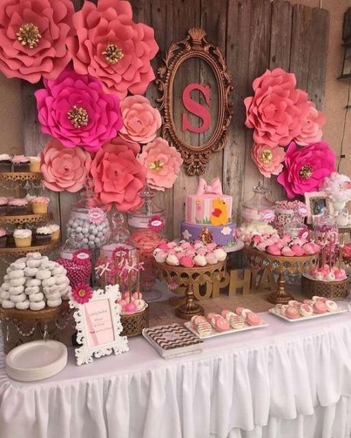 Painel de madeira com flores de papel em vários tons de rosa