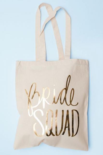 """Bolsa de pano com a frase """"Bride Squad"""" escrita."""