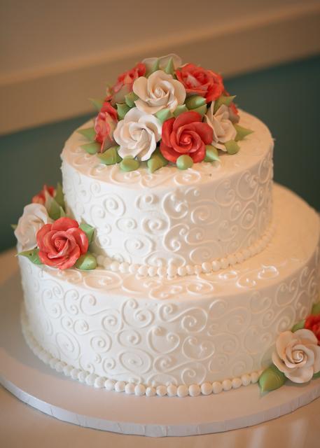 Bolo de dois andares decorado com rosas brancas e laranjas