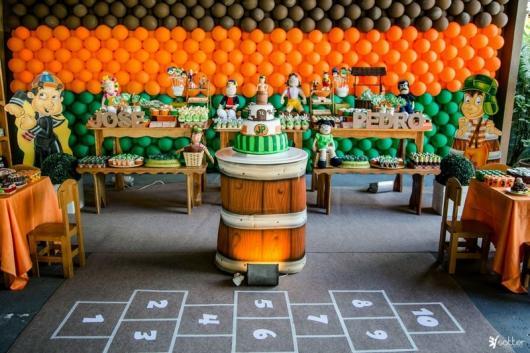 Linda ideia para um espaço grande com uma linda mesa, o fundo de balões, o barril e até a amarelinha