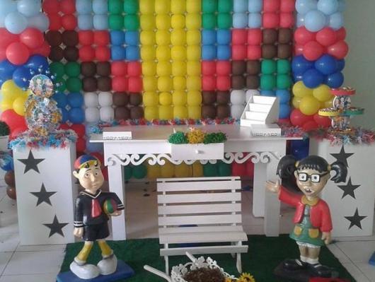 Os bonecos à frente da mesa e do painel valorizam a decoração