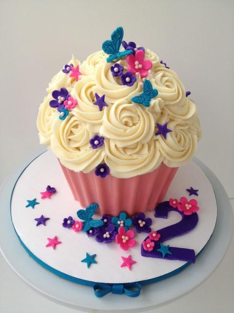 Cupcake rosa gigante coberto com chantilly amarelo bebê