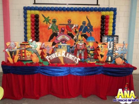 Painel desenhado com balões e a mesa forrada com vários moldes dos Power Rangers