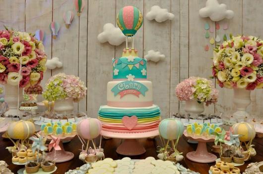 A mesa de doces e do bolo pode ter elementos delicados em cores pasteis