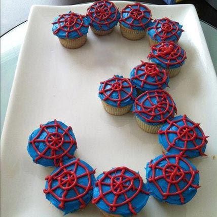 Cupcakes com massa azul e teia vermelha para uma festa de aniversário infantil