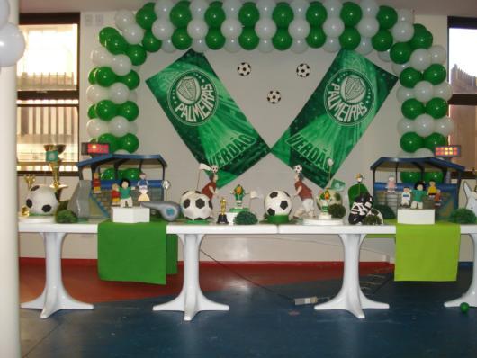Uma mesa branca com vários elementos verdes em destaque + painel de balões