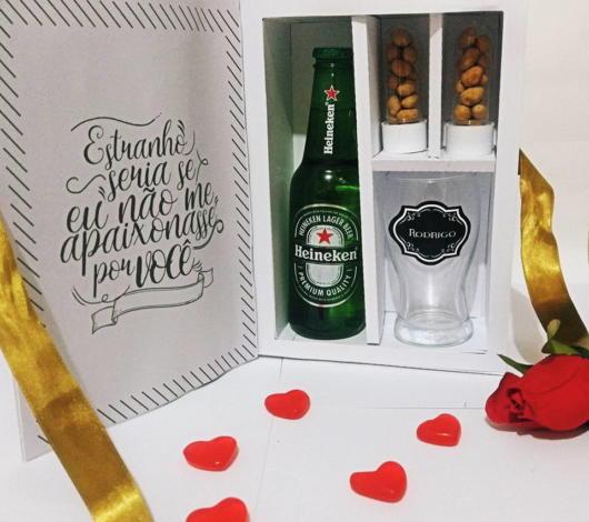 Essa caixa simples tem uma garrafa de cerveja, taças e petiscos