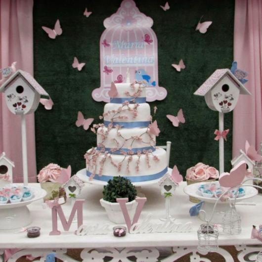 Festa rosa com borboletinhas, bem como casinhas de pássaros
