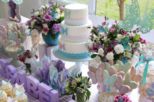 Detalhe da mesa de festa de 1 aninho com flores, bem como borboletas