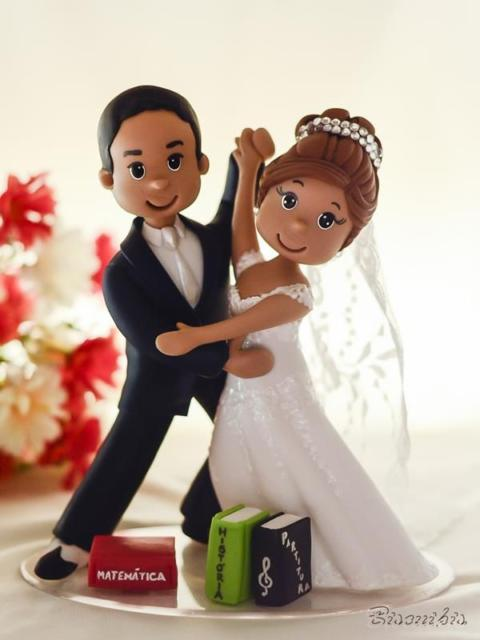 Noivinhos dançando para topo de bolo de casamento
