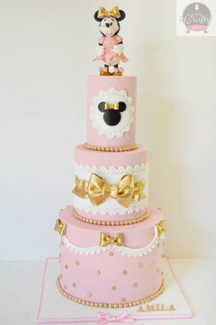 Bolo com camadas decoradas em rosa, branco e dourado.
