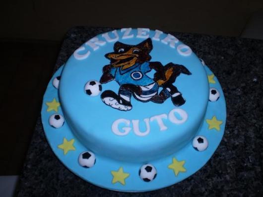 Um bolo todo azul com detalhes inerentes ao futebol