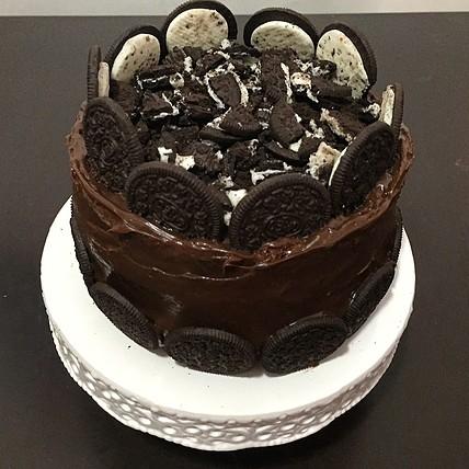 Veja bolo com cobertura de ganache de chocolate e biscoitos recheados