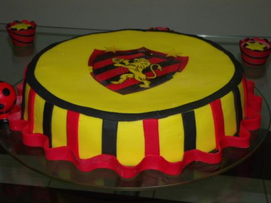 Bolo de pasta americana com base amarela e detalhes em preto e vermelho