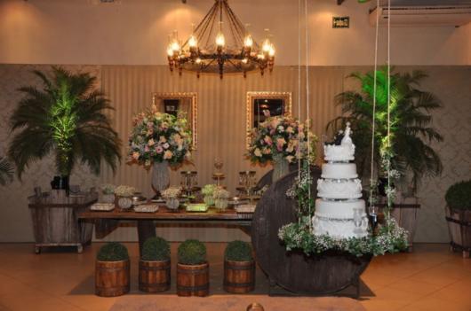 O bolo suspenso fica junto à mesa para dar o toque certo ao centro da festa