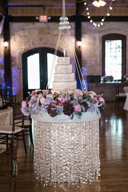 Lindo bolo de vários andares em um suporte com brilhos e flores
