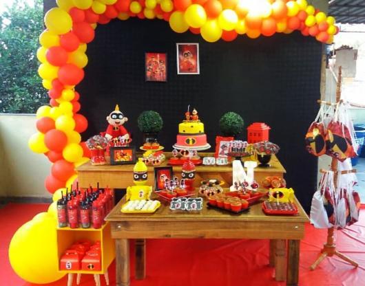 Um arco grande de balões amarelo e vermelho na festa Os Incríveis provençal