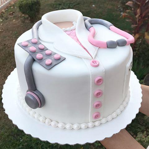 Bolo em forma de jaleco com botões rosas