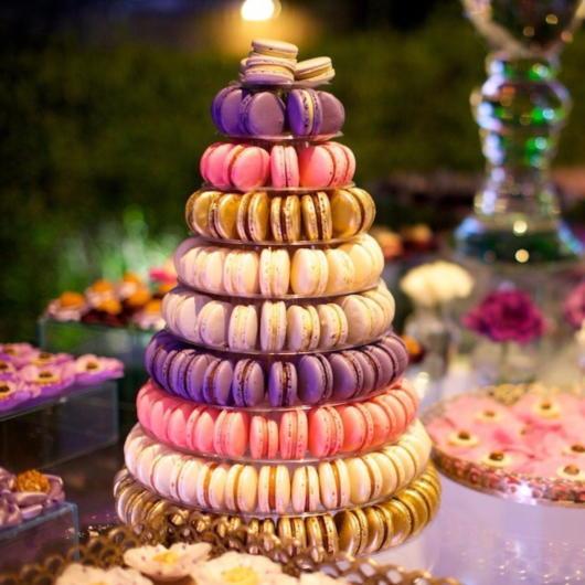 Torre de macarons com fileiras da cor dourada, rosa, lilás e creme.