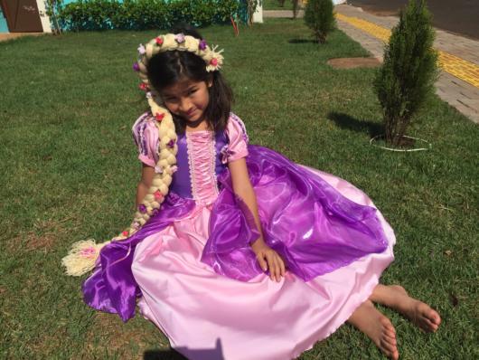 Criança sentada no chão para fazer pose com o vestido rapunzel.