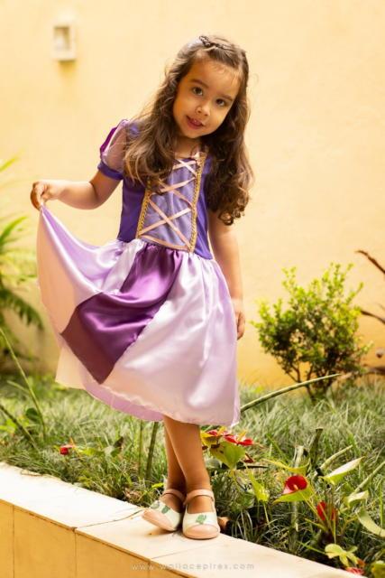 Criança segurando a saia da fantasia rapunzel fazendo pose.