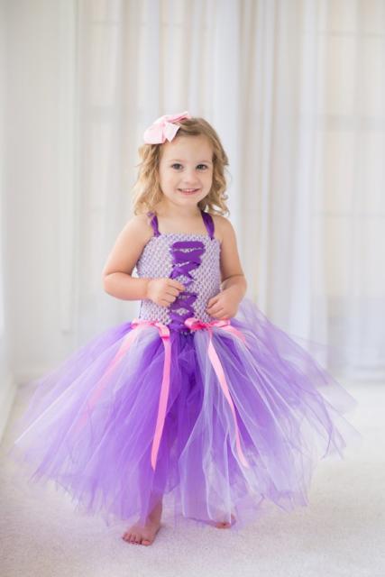 Fantasia de Rapunzel lilás com laços em rosa.